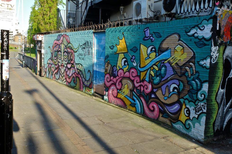 Far mural by Amara Por Dios.  Near mural by Artista.