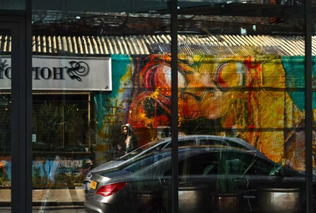 Reflection of Himbad mural and shop front of Shoreditch Junk on Sclater St, London E2